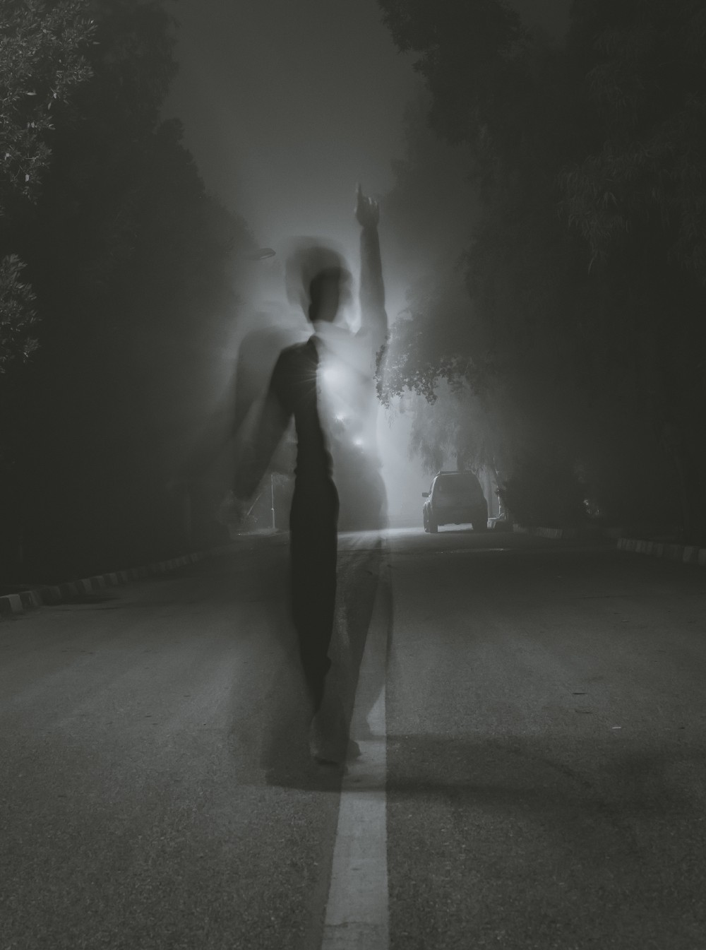 Shadowed person on a road in fog with one arm lifted. In the background, a car driving away.