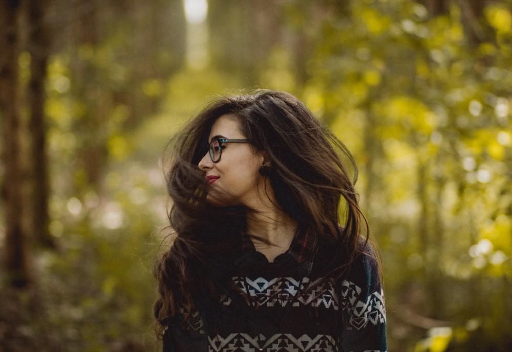 Woman wearing glasses tossing her hair in nature.