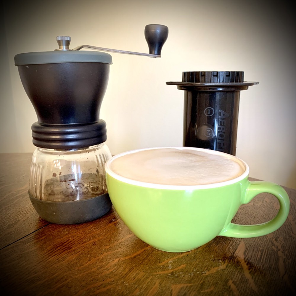 coffee grinder, aeropress, and a latte