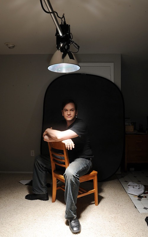 A man with dark hair & pale skin sits backwards on a chair on a dark room, lit dramatically from above.