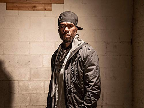 "A photo of Curtis ""50 Cent"" Jackson, in a grey shirt, Black jacket, and backwards Black baseball hat."
