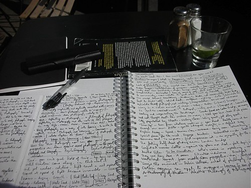 Open notepad with lots of writing and a pen