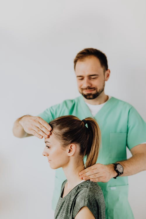 Picture of man applying relief to a female by giving her a head massage.