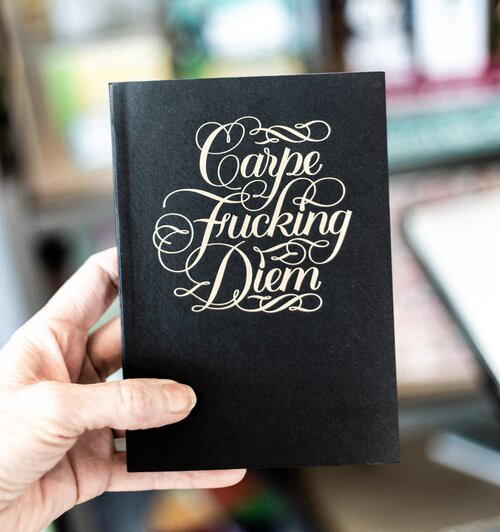 person holding Carpe Fucking Diem book