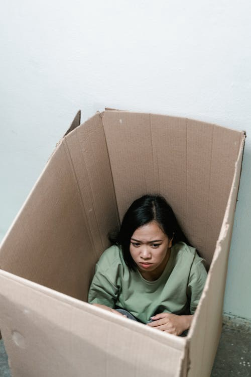 Woman trapped in a box and looking pretty afraid.