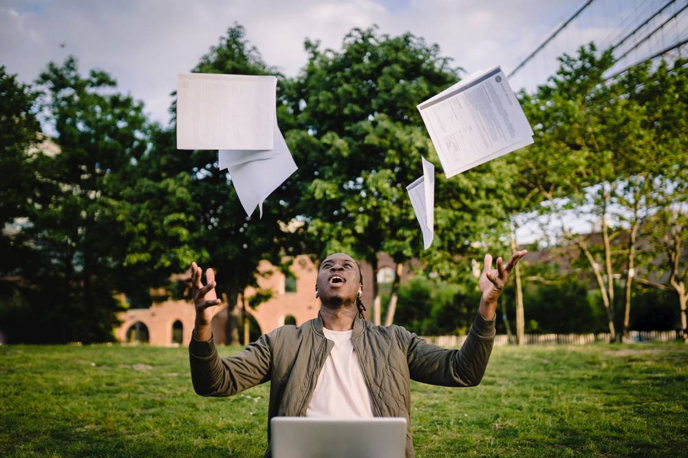 A man that's outside with a computer in his lap throwing papers into the air