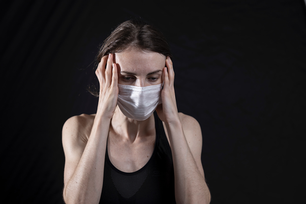 Woman wearing facemask, looking anxious