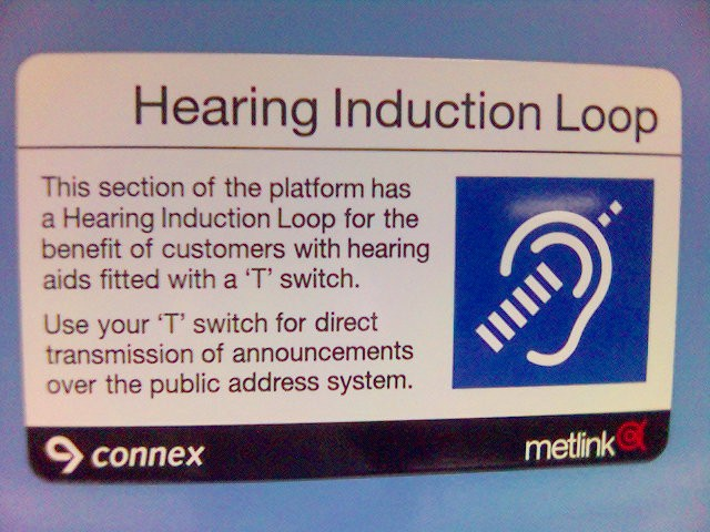 A sign in a train station advising travellers that the public announcement system broadcasts with a hearing induction loop, to allow travellers with a hearing aid to tune into announcements directly with their hearing aid's receiver. Courtesy Wikimedia commons user avlxyz.