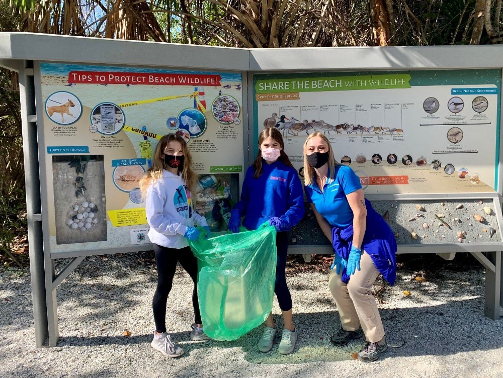 3 people pose with green garbage bag in front of 2 panel sign