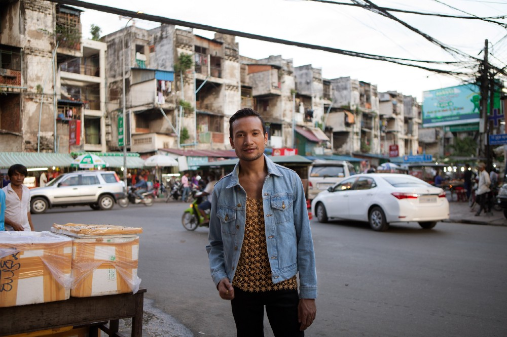 Ok poses on sidewalk of busy street, wearing a patterned shirt, denim jacket and black pants