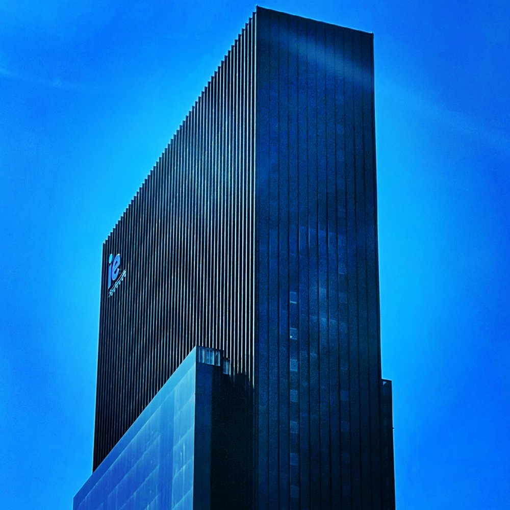 IMAGE: A diagonal view of the top of the IE Tower in Madrid on a blue sky.
