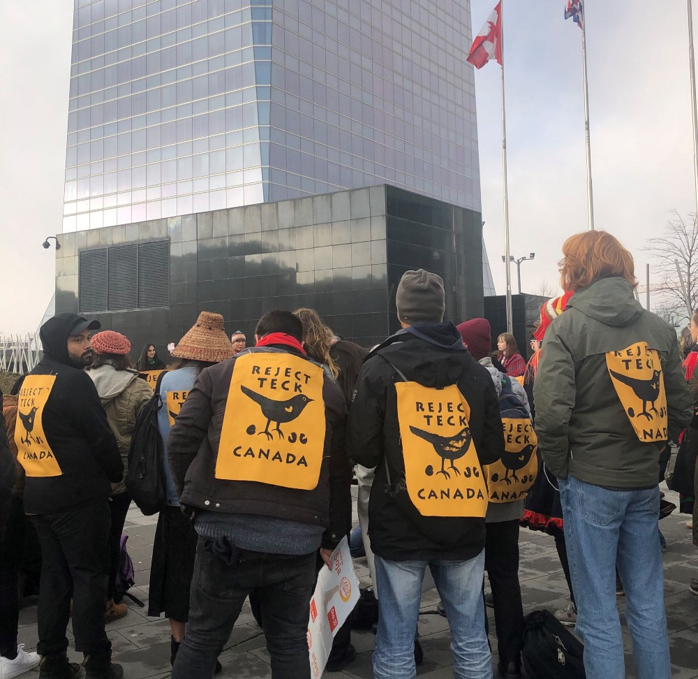 """Four activists standing outside of the Canadian embassy building in Madrid, Spain, with signs on their backs """"Reject Teck"""""""