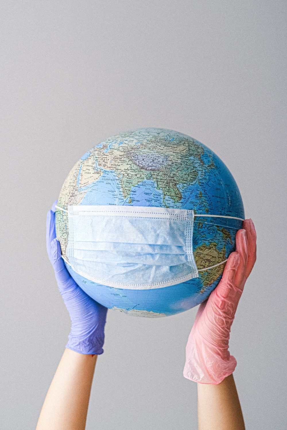 Photo by Anna Shvets from Pexels https://www.pexels.com/photo/hands-with-latex-gloves-holding-a-globe-with-a-face-mask-41675