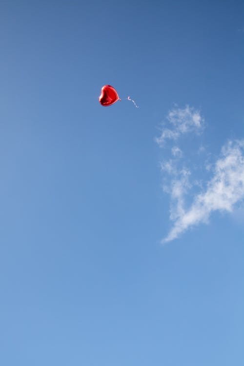 A red, heart-shaped balloon floating in the sky past a heart-shaped cloud.