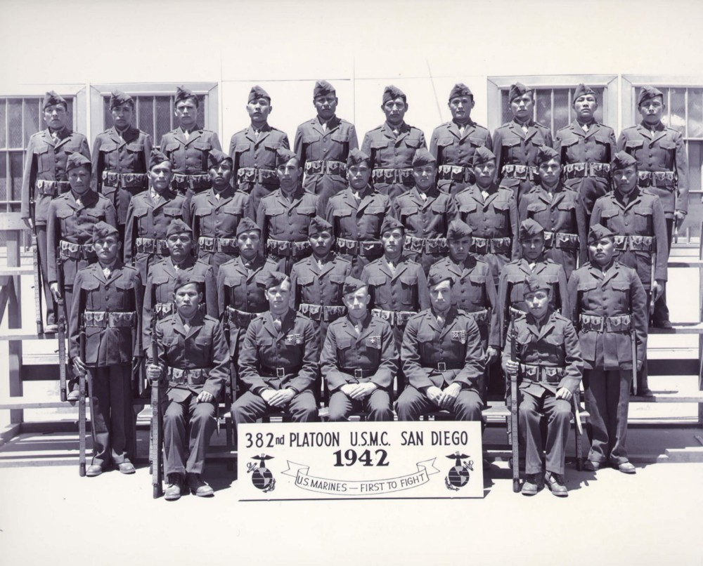 Men pose in uniform for a formal photo with a sign that says 382nd platoon USMC San Diego 1942