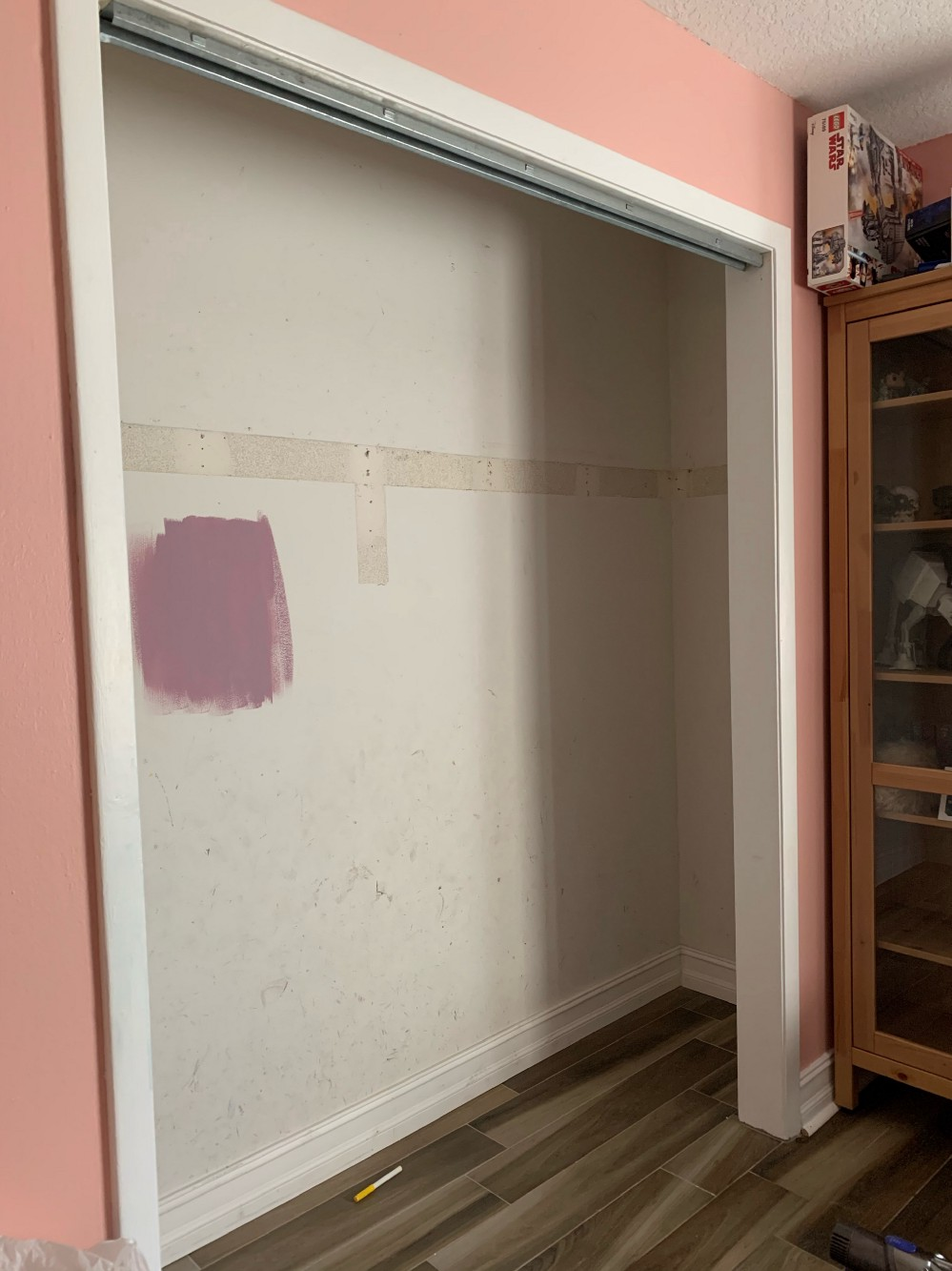 Closet, bare. The outline of the shelf that used to be there is visible on the wall. There is a pinkinsh/purple sample of paint on the wall. Outside of the closet the trim is white, the room is pink (Rachel pink by Sherwin Williams) and the floors are a wood look tile.