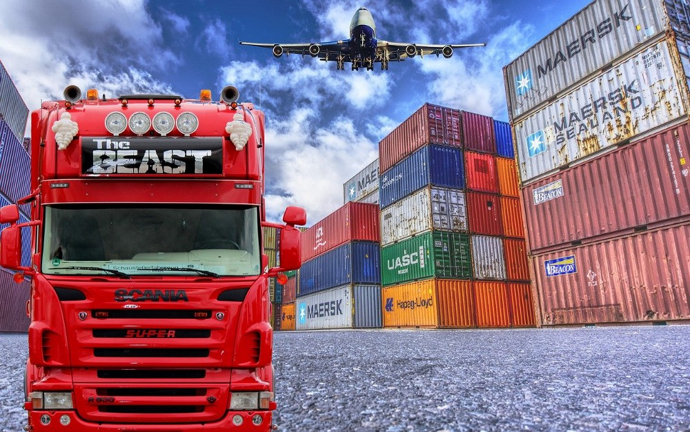 IMAGE: A big truck, a pile of containers and a plane passing by