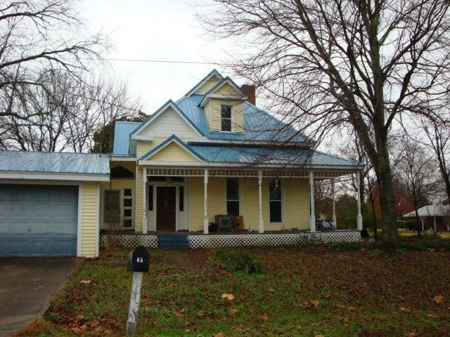 Photo of an average suburban house, yellow paint and blue roof. Two stories.