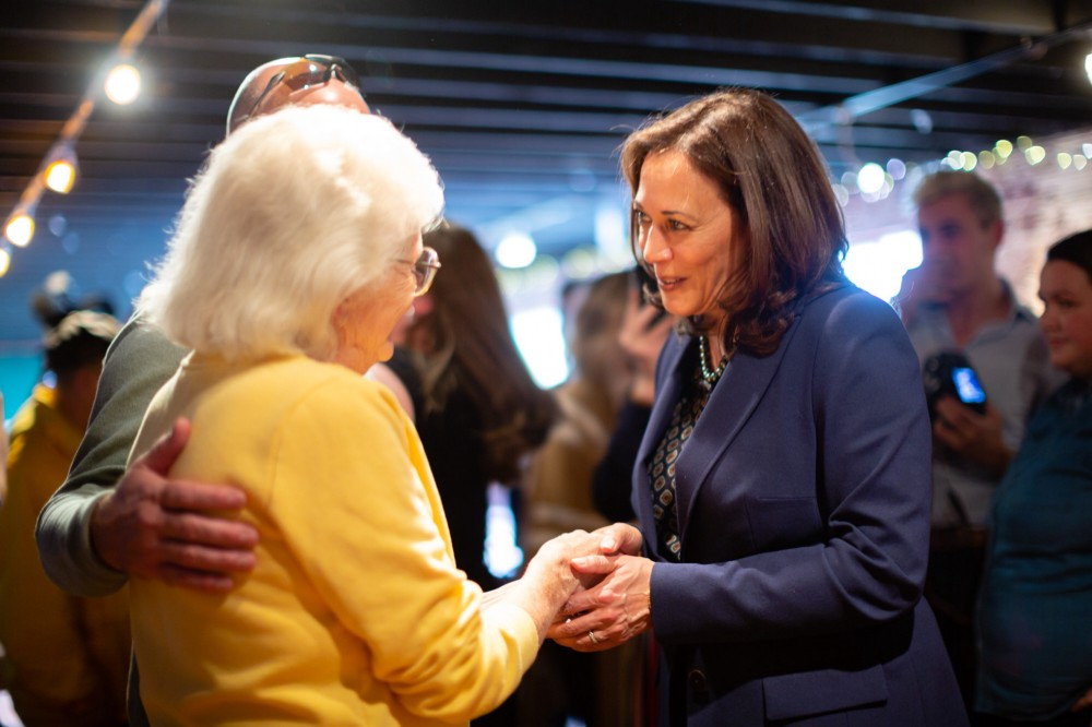 Kamala Harris in a blue suit holds the hands of a senior Iowa caucus-goer in a yellow sweater
