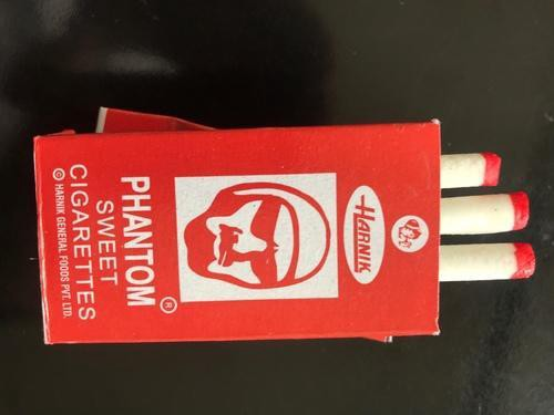 A red box of white candy cigarettes, a distinctive drawn face is the logo