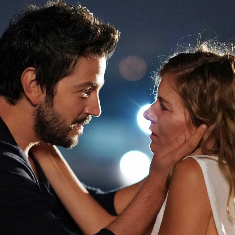 Diego Luna holds Sienna Miller's face in his hands, comfort.