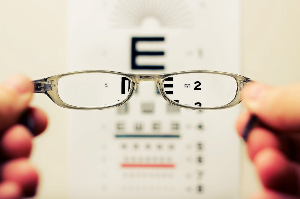 A man holding up a paid of glasses to show a Snellen chart in the background