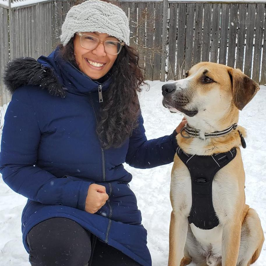 Catherine smiles and kneels next to Mickey (a beige and white medium-sized dog) in the snow