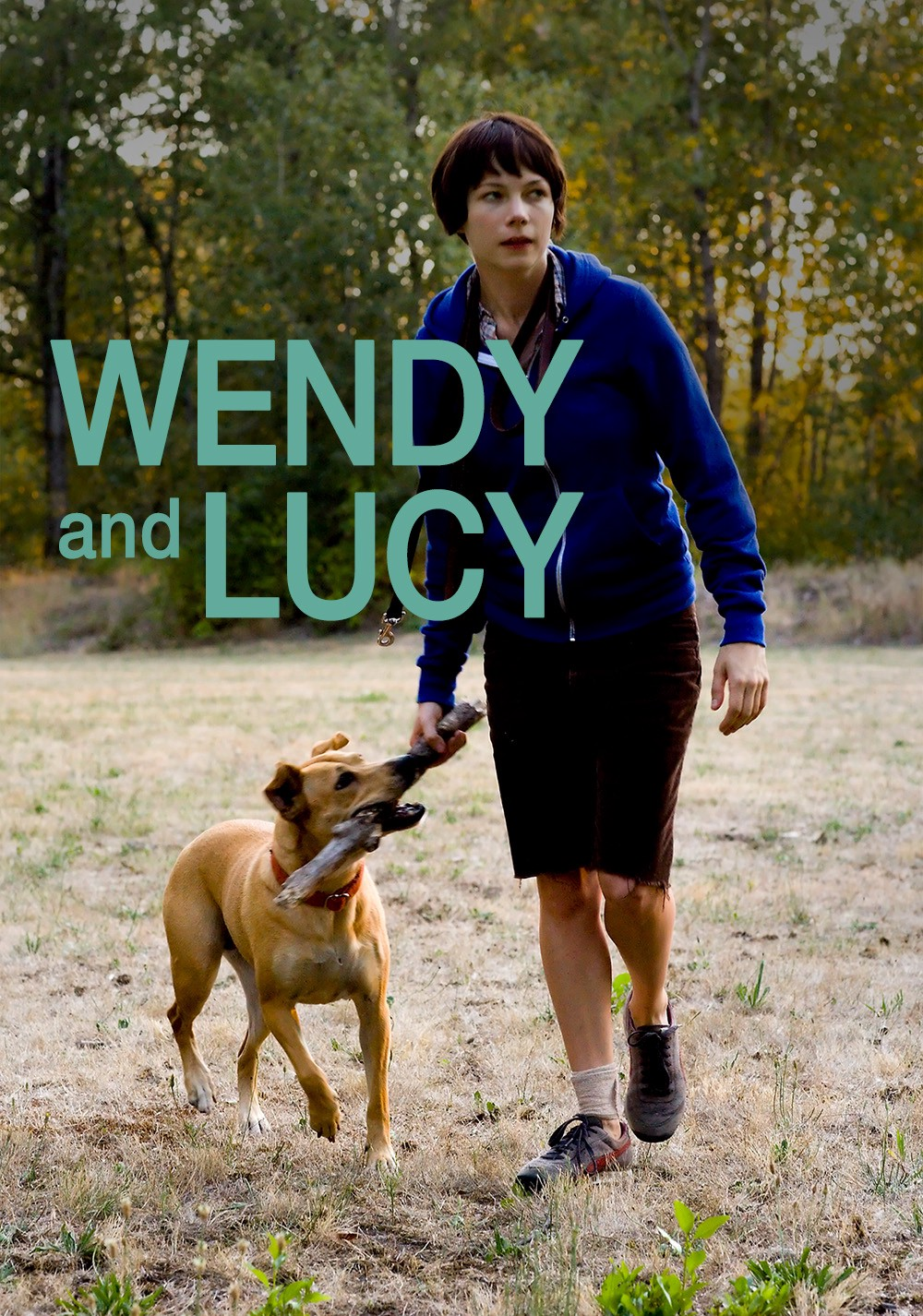 A woman in a blue jacket plays fetch with her dog.
