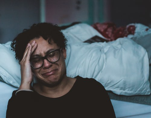 A woman crying on the side of her bed.