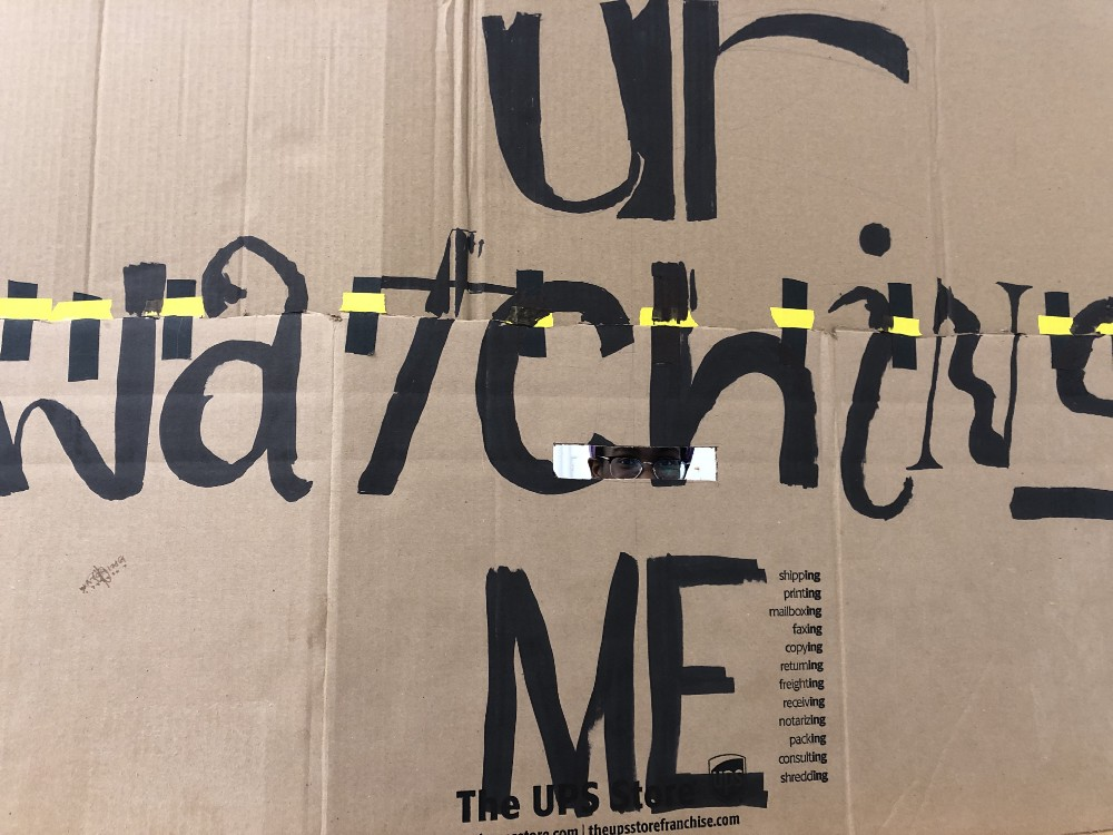A painted cardboard panel with the words 'ur watching me'