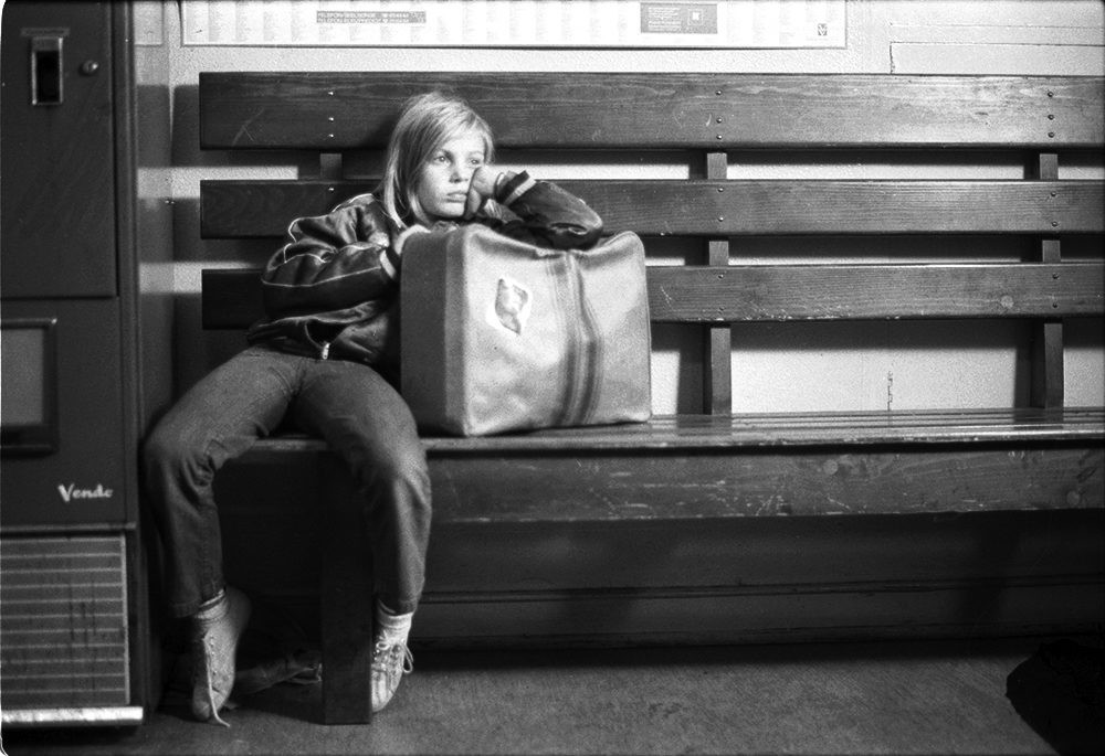 A little girl slumps against her suitcase while sitting in a bus station.