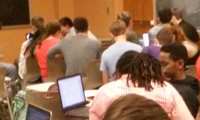 An image of students working in groups in a class.