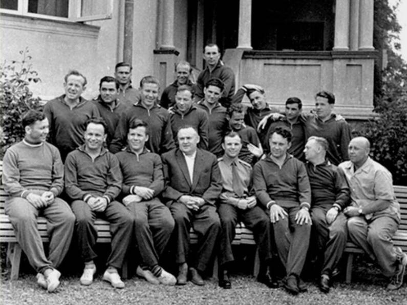 A group of men in zip-up uniforms and several older men in suits posing for a photo