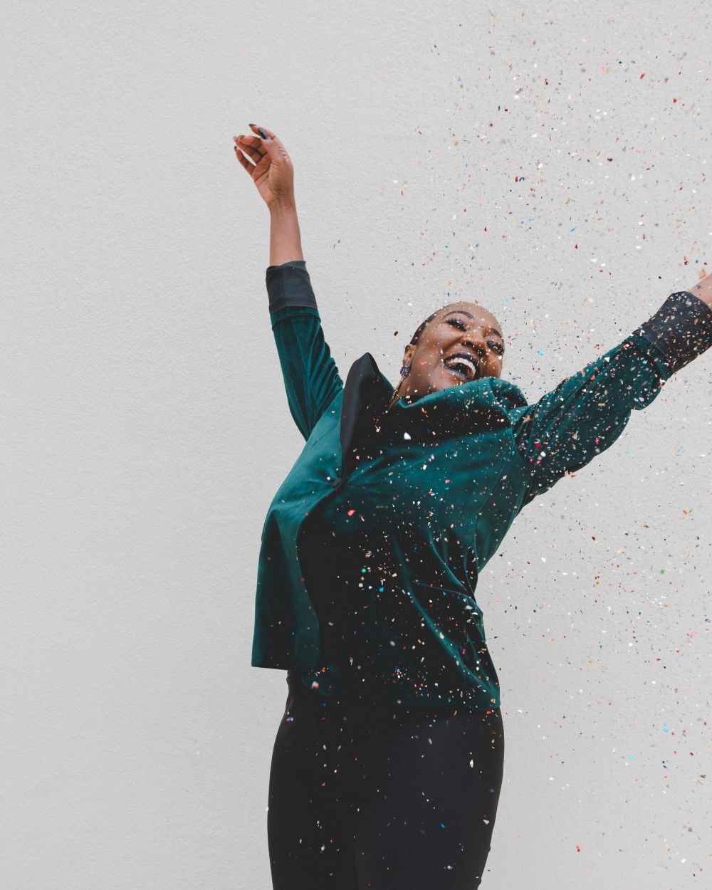 A joyous black woman dressed in a velvet green jacket sprinkles confetti in the air.