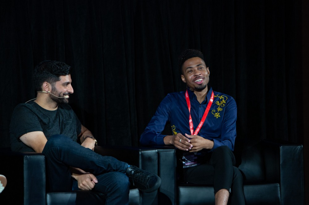Nima Ghamsari, a Persian man in a black t-shirt, and Ulyssses Smith, a Black man in a blue collared shirt, on stage