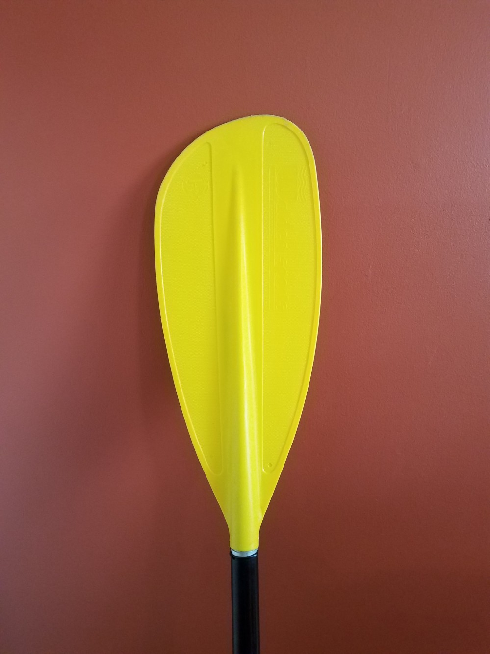 A bright yellow boat paddle leaning against a red wall
