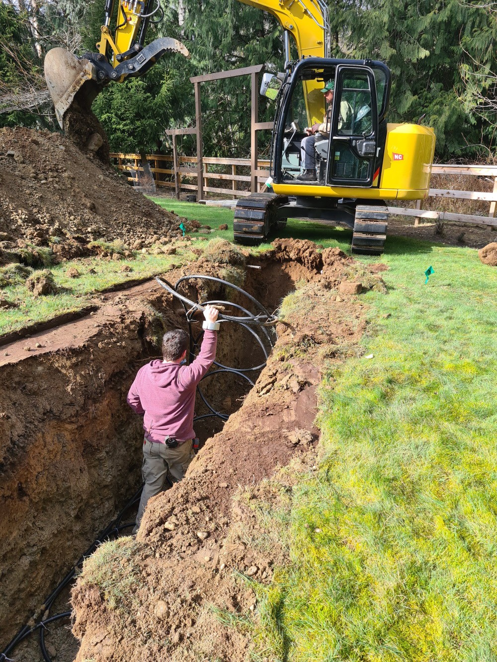 Excavator digging a trench through the yard, installer standing in the trench, shorter than the sides.