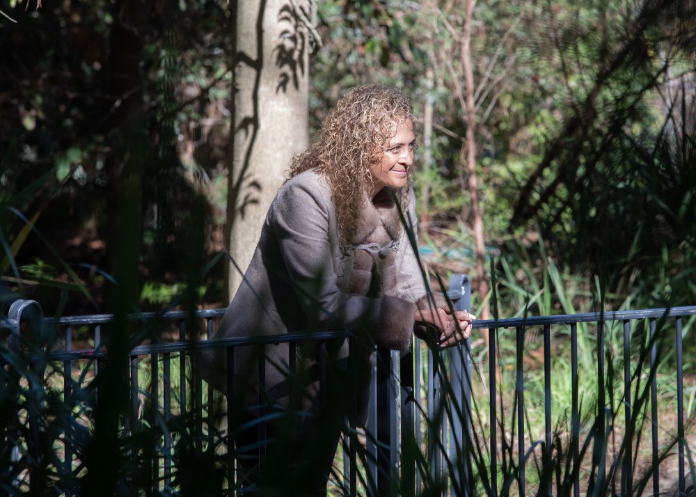 Dr Samantha Pillay looks out from a small bridge across the gardens.