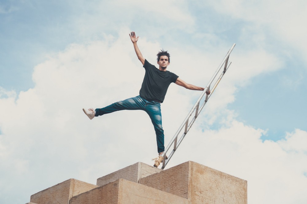 Man in black shirt and jeans balancing on ladder on top of concrete structure.