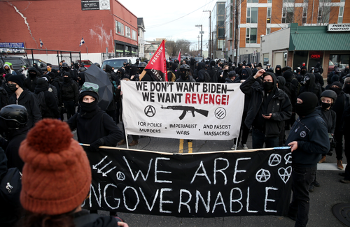"A crowd of black-clad protestors wearing masks carry signs that say ""We don't want Biden, we want revenge, for police murders, imperialist wars, and fascist massacres."" ""We are ungovernable."""