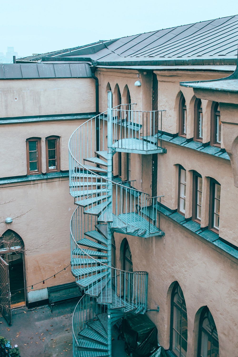Patina spiral staircase on side of European building
