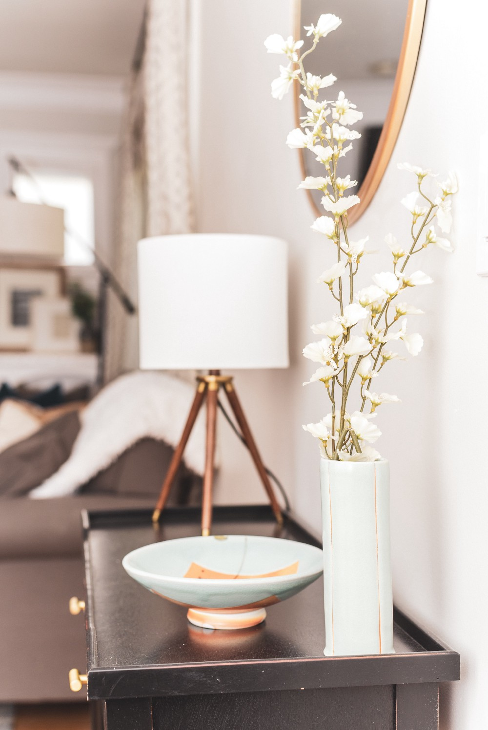 Vignette of a side table with a vase of small white flowers next to a celadon glazed bowl and a small table lamp