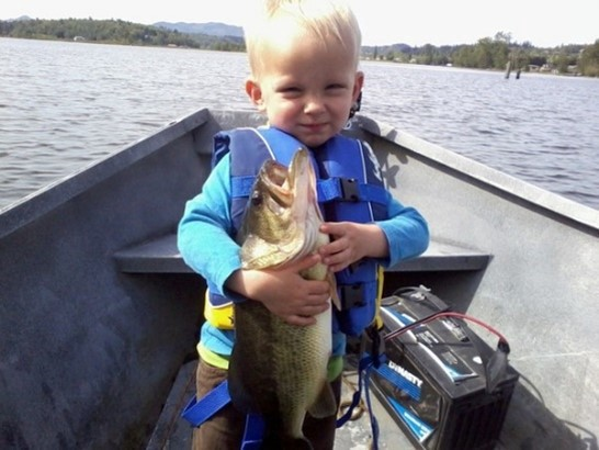 You child on a boat wearing a life jacket holding a large bass vertically