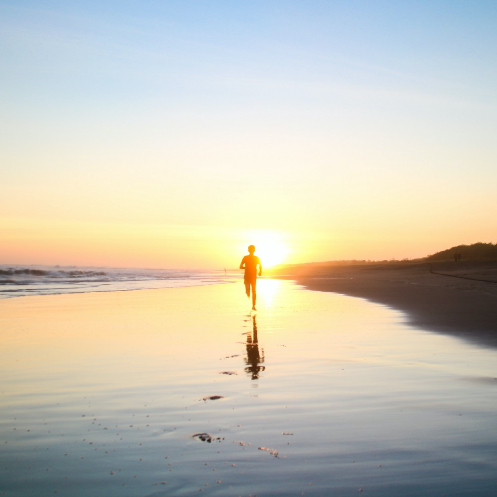 silhouette of boy running along a beach into the sunset