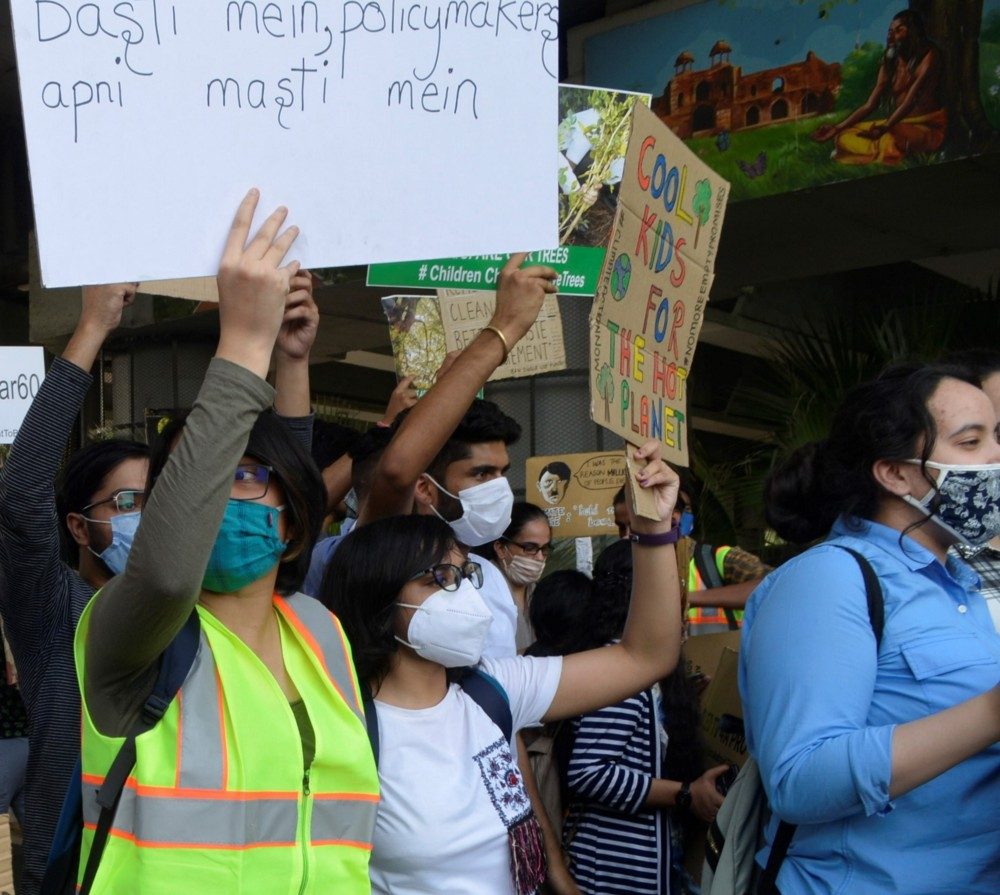 """Oindrila holding a sign that reads """"Cool kids for the hot planet"""" while striking for climate justice policy reform in New Delhi, India."""
