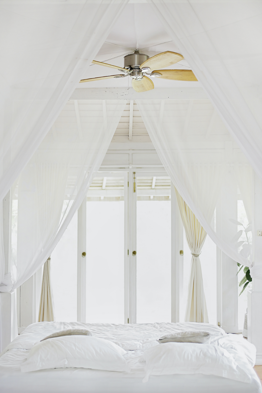 Bright and airy bedroom with all white bedding and white sheer draped canopy overlooking French doors to a balcony