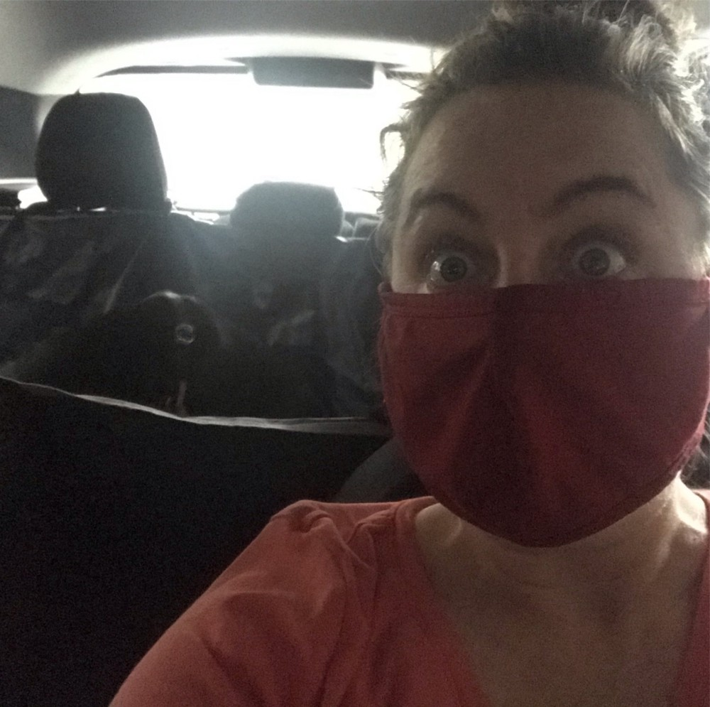 Masked woman looks terrified driving a car