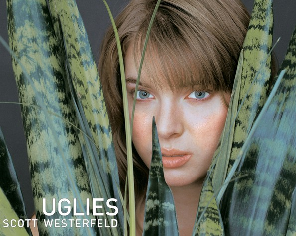 """A young white girl stares at the camera from among the large leaves of a plant. """"Uglies"""" is written in white font."""