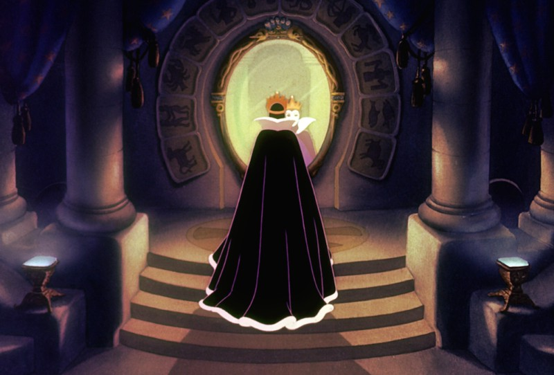 The evil queen in Snow White stands in front of the mirror