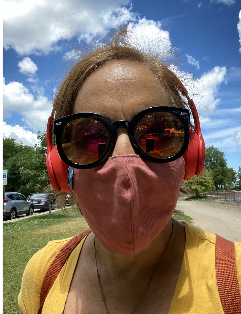 A photo of a woman wearing a mask, big sunglasses and red beats headphones